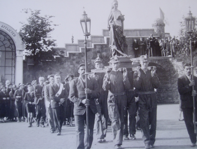Two Goanese torch bearers and four miners in overalls and mining hats, carrying the statue of St Barbara, c. 1931. Reproduced with permission of Carfin Shrine Archive, Motherwell.